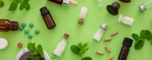Homeopathy concept. Glass bottles and vials with homeopathic globules, liquid substance and fresh herbs, green background. Alternative herb medicine healtcare, flat lay